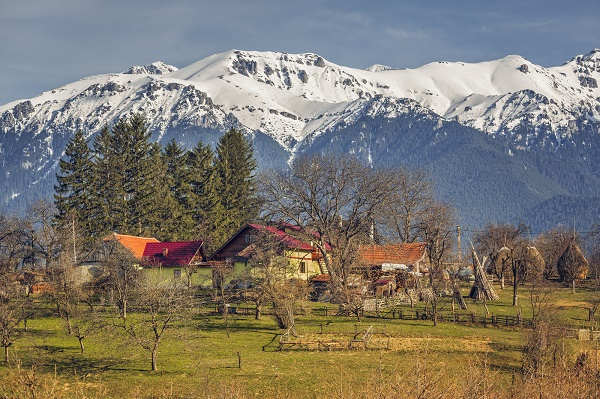 Spring sunny rural landscape with snowy Bucegi mountains and traditional Romanian houses and farm in Predelut village, near Bran, Transylvania region, Romania.
